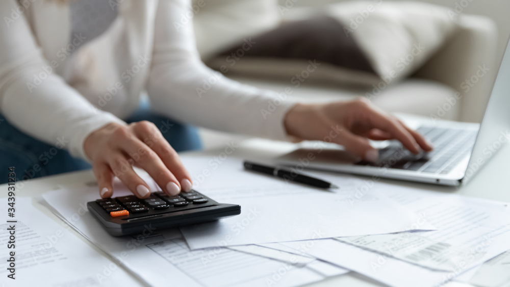 Fototapeta Close up of woman busy paying bills online on computer calculating household finances or taxes on machine, female manage home family expenditures, using calculator, make payment on laptop