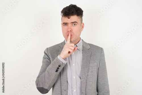Photo Dont tell my secret or not speak too loud, please! Emotional surprised student makes hush gesture, asks be quiet, has scared expression as afraids of revealing secret, poses against gray studio wall