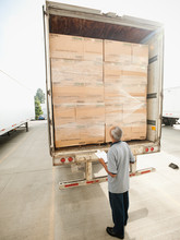 Man Checking Load On Truck Trailer