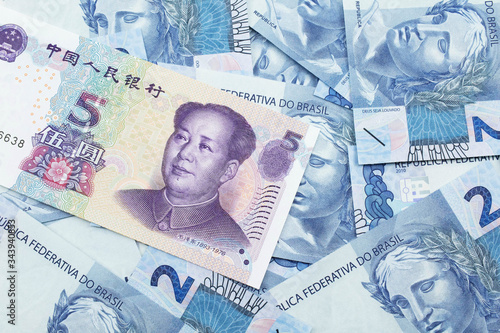 Obraz na plátne A close up image of a purple, five Chinese yuan bank note, close up on a background of blue Brazilian two reais bank notes