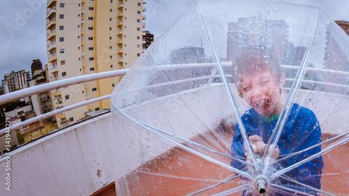 Fotografia, Obraz Niño juega con un paraguas en terraza dia lluvioso