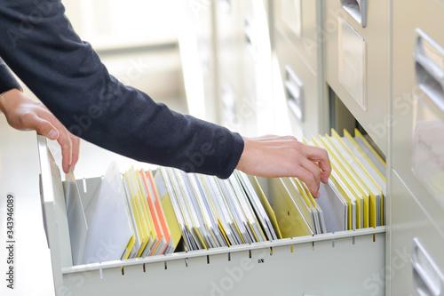 机の引き出しの中から、書類を探している手のアップ Wallpaper Mural