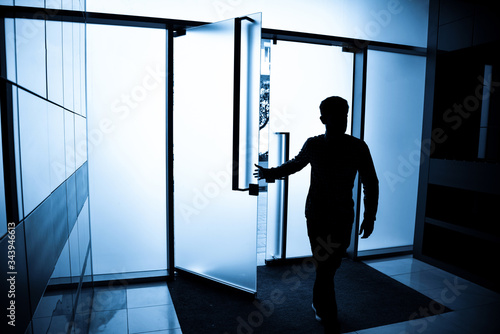 persona in silhouette entra nell'androne di un palazzo dal  portoncino vetrato Canvas Print