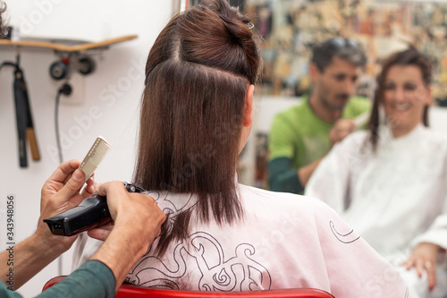 Professional hairdresser cutting hair and making a hairstyle to a young brunette woman with cordless hair trimmer at the hairdresser salon.