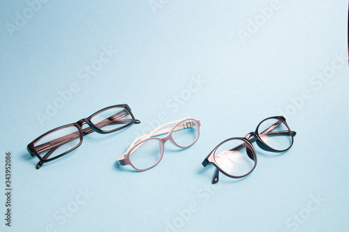 Photo several pairs of different glasses for vision correction on a blue background; c