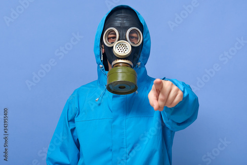 Closeup portrait of ecologist frights with factories which pollute air, water, forests and land, scientist wearing uniform and respirator, pointing to camera with with fore finger against blue wall Wallpaper Mural