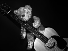 Close-up Of Teddy Bear On Guitar Against Black Background
