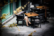 Woman Reading Newspaper While Sitting On Chair In Cafe