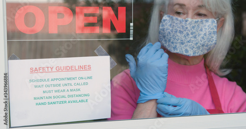 With cautious optimism a mature small business owner wearing a face mask and disposable gloves posts safety rules as she reopens her store after the coronavirus shutdown Fototapet