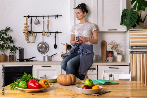 Young and beautiful housewife woman cooking in a white kitchen - 343967063