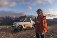 Young Woman Looking Down At Camera In Front Of Car In Mountains