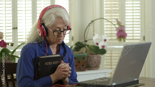 Fotografía An older woman holding a Bible and praying as she attends church virtually via her laptop due to congregation and group fellowship restrictions during COVID19 pandemic