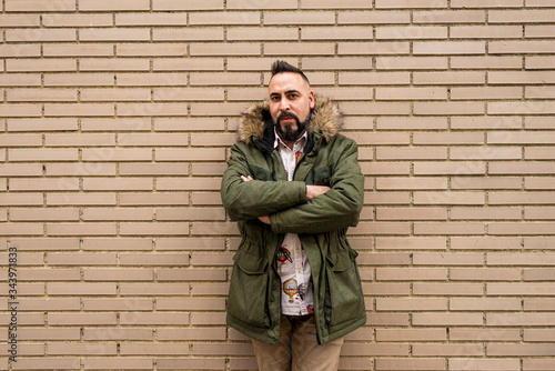 Bearded male with crossed arms leaning on bricked wall, looking camera - 343971833
