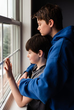 Side View Of Siblings Looking Through Window