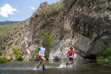 Two Men Running Across A River...