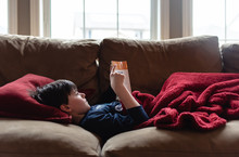 Young Boy Reading A Book On A ...