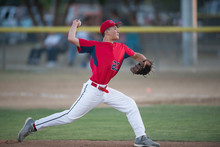 Teen Baseball Player Pitcher In Red Uniform In Full Wind Up On The Mound