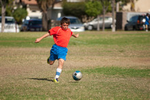 Young Soccer Player In Red Blue Uniform Kicking Soccer Ball In Park