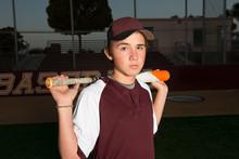 Portrait Of A High School Baseball Player In Maroon Uniform Holding His Bat