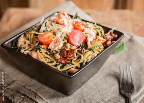 Fototapeta miska włoskiego makaronu spagetti z łososiem, pomidorkami koktajlowymi, suszonymi pomidorami i szpinakiem obraz