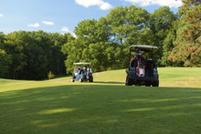 Two Golf Carts Ride Off To Their Next Destination On A Beautiful Golf Course One Summer Afternoon