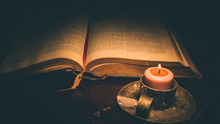 High Angle View Of Lit Candle And Bible On Table In Darkroom