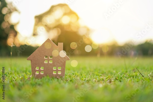 Fototapeta Closed up tiny home model on green grass with sunlight background. obraz