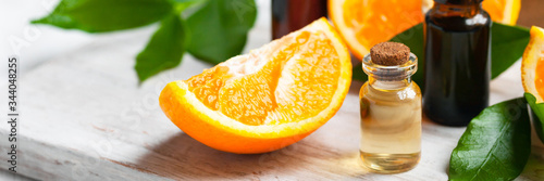 Concept of natural organic orange essential oil for skin face, body health care. Moisturizing, aromatherapy, detox treatment, anti-stress effect. Fresh fruit, green leaves, white background. Banner
