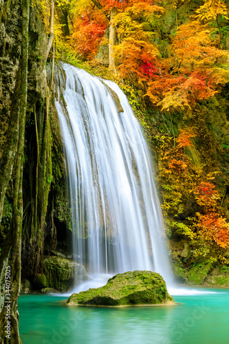 Fotografering Colorful majestic waterfall in national park forest during autumn