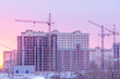 winter morning, the construction of multi-story frame houses with tower cranes, freezing construction