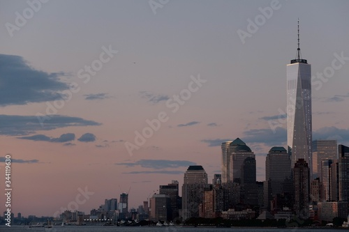 Cuadros en Lienzo One World Trade Center Amidst Buildings In Front Of River Against Sky At Dusk