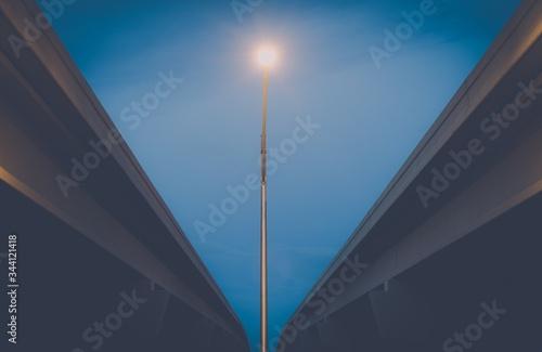 Fototapeta Low Angle View Of Cropped Bridges And Lit Street Light Against Blue Sky obraz na płótnie