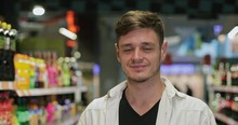 Close Up View Of Millennial Happy Man Looking To Camera While Standing At Soft Drink Section. Portrait Of Young Guy Posing And Smiling In Shop. Concept Of Shopping And Real Life