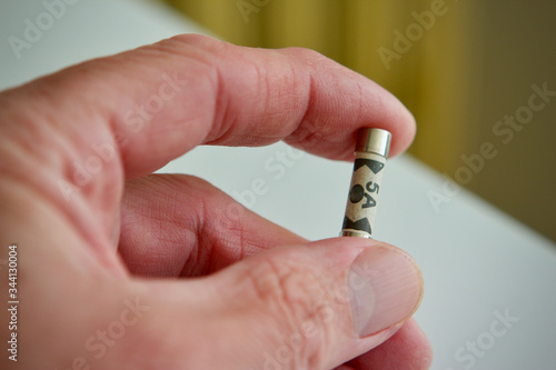 Photo 5 amp plug fuse held by a mans hand