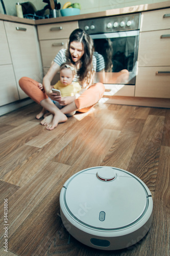 Photo Mother and daughter using robot vacuum cleaner stock photo