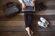 businessman sitting on wooden floor with briefcase, notebook,