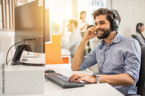 Fotomural Smiling friendly handsome young male call centre operator.