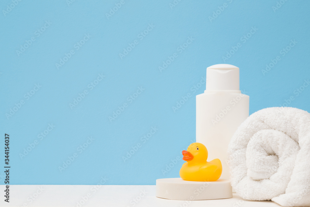 Fototapeta White shampoo bottle, towel and wisp. Yellow rubber duck. Body washing concept. Close up. Front view. Empty place for text or logo on light blue background. Pastel color.