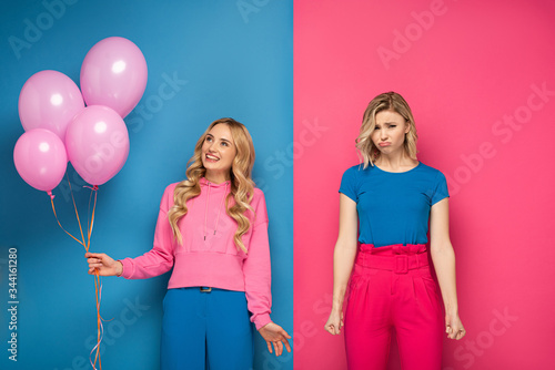 Smiling blonde girl holding balloons near sad sister on blue and pink background