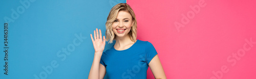 Fotografie, Tablou Panoramic orientation of positive blonde girl waving hand at camera on pink and