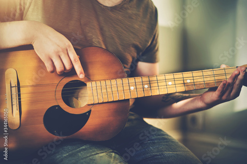 An aspiring young musician plays a tune on a very old dilapidated acoustic guitar, illuminated by sunlight Wallpaper Mural