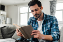 Selective Focus Of Handsome Man In Plaited Shirt Reading Book At Home