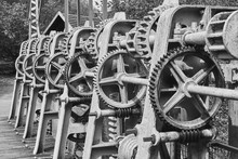 Gear Wheels, Toothed Belts, Chains, Shafts And Racks At A Weir On The River Aller, Germany, Black And White