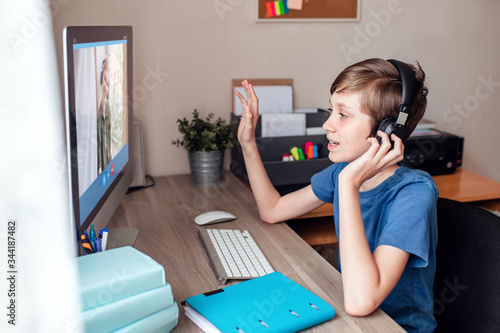 Photo A teenage boy communicates with relatives via a web camera video conference on the computer at home