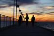 Silhouette People Walking On Pier Over Sea At Sunset
