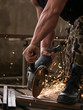 Worker cutting metal with grinder. Sparks while grinding iron. man work in home workshop garage with angle grinder, goggles and construction gloves, sanding metal makes sparks closeup, diy and concept