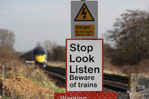 Beware of trains signs with train in the background Wallpaper Mural