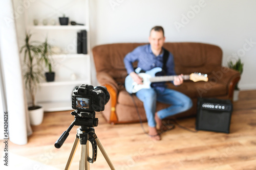 Photo A young guy is recording how to play guitar video tutorial, he is sitting on a couch with an electric guitar, a combo amp is near