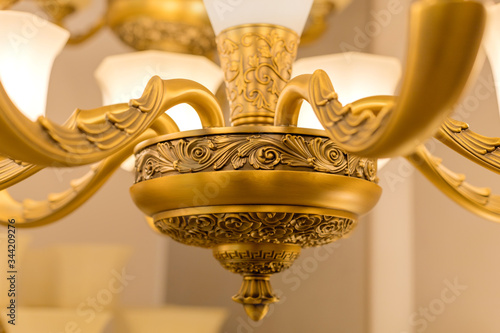 A part of lower part of the gold-colored armature of ceiling chandelier in the switched-on state with white matte plafonds Canvas Print