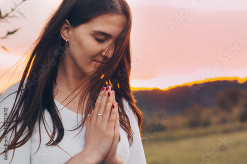 Portrait of a single woman praying and looking down at sunset Canvas-taulu